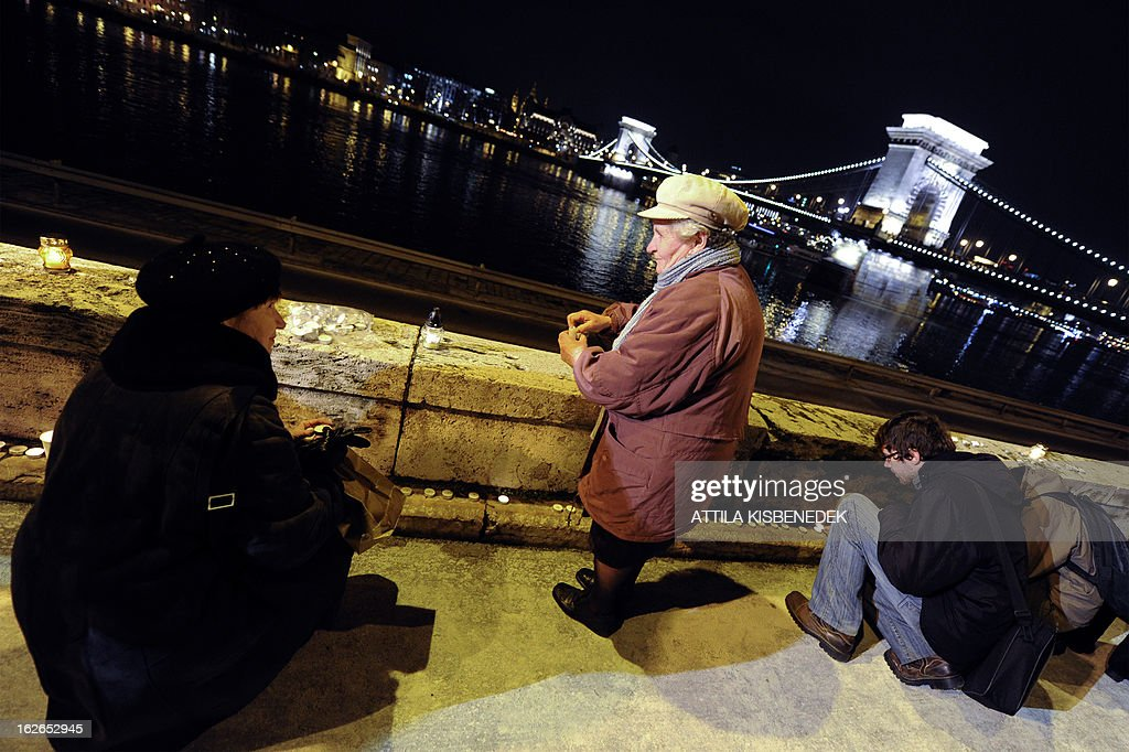 People light candles at the bank of Danube River in Budapest near the Chain Bridge, the oldest Hungarian bridge on February 25, 2013 during a memorial day for victims of communist dictatorships.