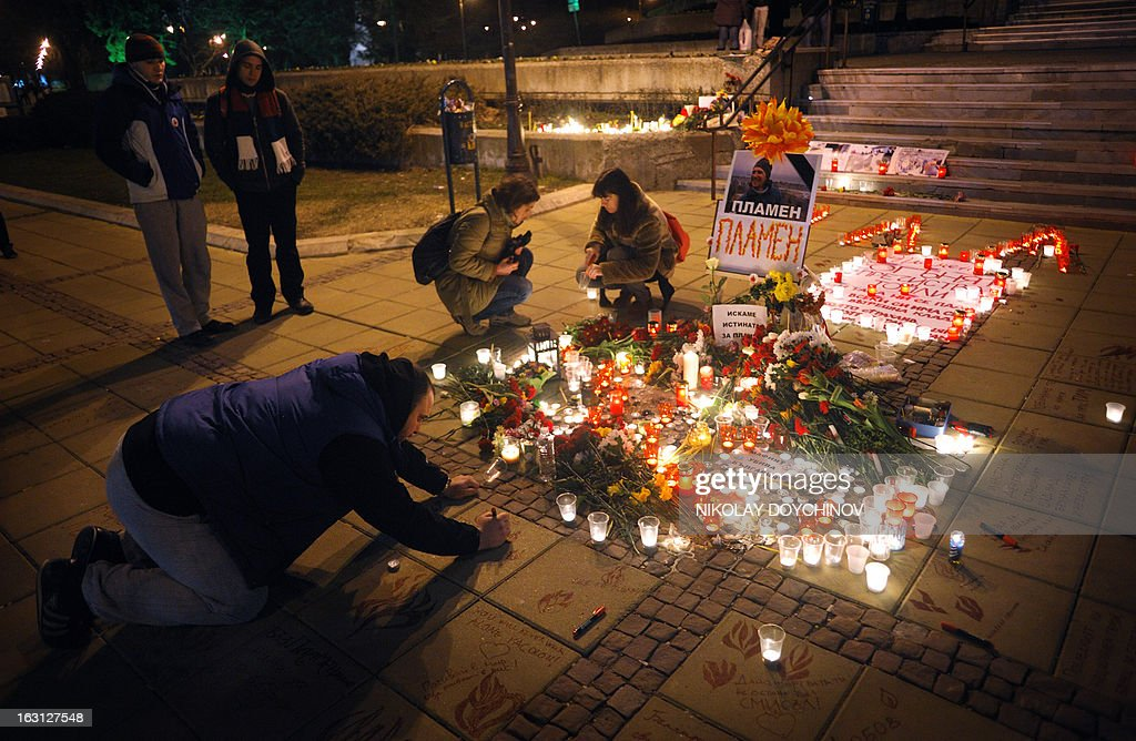 People light candles during a candlelight vigil on March 4, 2013 outside the city hall of Varna, on the site where a man who became a symbol of the three-week wave of protests against corruption, set himself on fire. Plamen Goranov, a 36-year-old amateur photographer and rock climber, died the day before after setting himself ablaze on February 20 in the Black Sea city of Varna. Goranov's self-immolation prompted Varna protestors to adopt his cause and turn their initial anger over high electricity bills against the long-time mayor, whom they accused of corruption and favouritism towards a local business group. AFP PHOTO / NIKOLAY DOYCHINOV