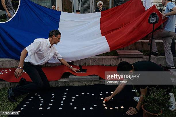 People light candles during a vigil for the victims of the attack in the French city of Nice on July 16 2016 in Hong Kong A FrenchTunisian attacker...