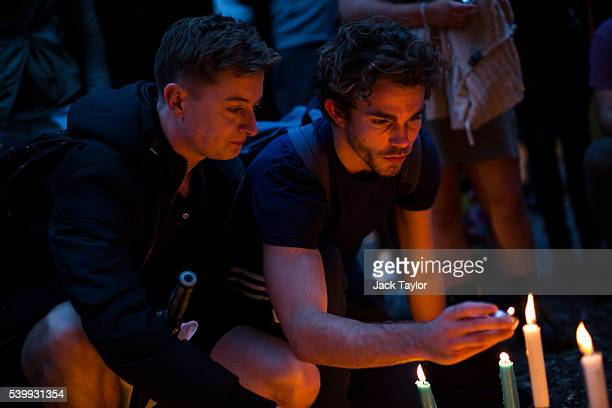 People light candles during a vigil for the victims of the Orlando nightclub shooting on Old Compton Street Soho on June 13 2016 in London England 49...