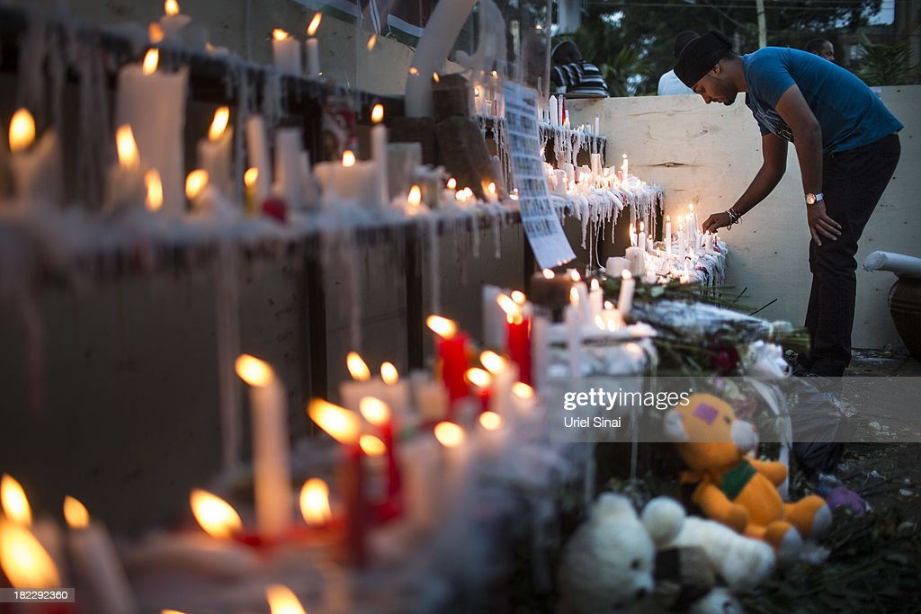 People light candles for the victims of the attack outside the Westgate Shopping Centre on September 29 2013 in Nairobi Kenya Officials begun the...