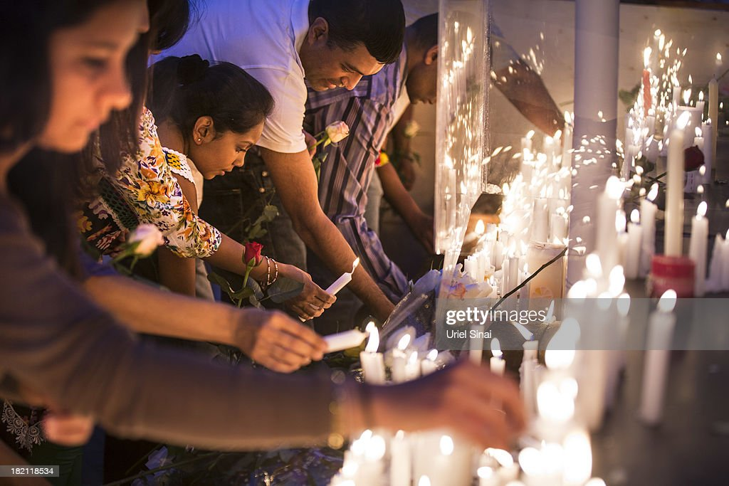 People light candles for the victims of the Westgate Shopping Centre attack on September 28, 2013 in Nairobi, Kenya. Officials begun the task of forensic probing the Westgate shopping mall following a four-day siege that killed at least 67 civilians and police and was claimed by the Somali militant group al Shabaab.