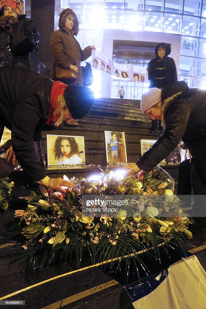 People light candles in front of the portraits of the victims during an homage called by UJSF (Union of Jewish Students in France) in Paris near the Opera-Bastille, on March 19,2013, to those slain by Al-Qaeda-inspired gunman Mohamed Merah whose shooting spree in and around Toulouse left seven people dead in March 2012. VERDY