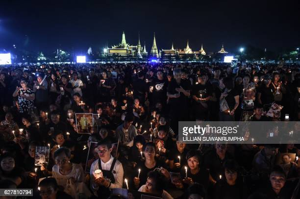 TOPSHOT People light candles in honour of the late Thai King Bhumibol Adulyadej to commemorate his birthday in Sanam Luang park in front of the Grand...