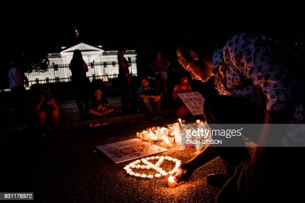 People light candles in the form of a peace sign in front of the White House on August 13 2017 in Washington DC for a vigil in response to the death...
