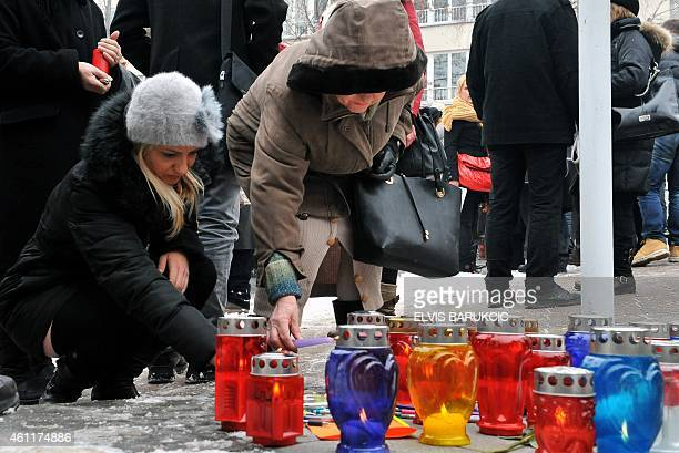 People light candles in the vicinity of French Embassy in Sarajevo on January 8 in tribute to the twelve people killed the day before in an attack by...