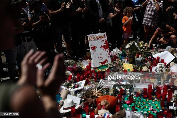 People light candles leave flowers and notes at La Rambla boulevard for the victims those who lost their lives in terror attack killing at least 13...