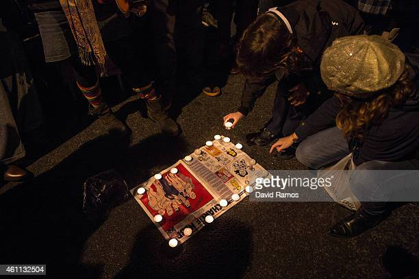 People light candles on a Charlie Hebdo Magazine during a gathering of people showing their support for the victims of the terrorist attack at French...
