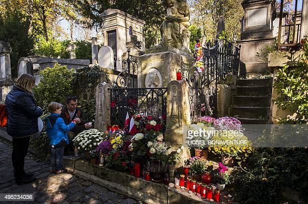 People light candles on the grave of Polish composer and pianist Frederic Chopin at the Pere Lachaise cemetery on November 1 2015 in Paris during the...