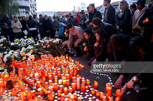 People light candles to commemorate the victims outside the nightclub Colectiv in Bucharest on October 31 a day after a mortal fire At least 27...