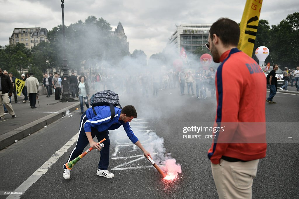 People light flares during a demonstration against controversial labour reforms, on June 28, 2016 in Paris. Unions have called repeated strikes and marches in opposition to the law, which seeks to bring down France's intractable 10-percent unemployment rate by making it easier to hire and fire workers. / AFP / PHILIPPE