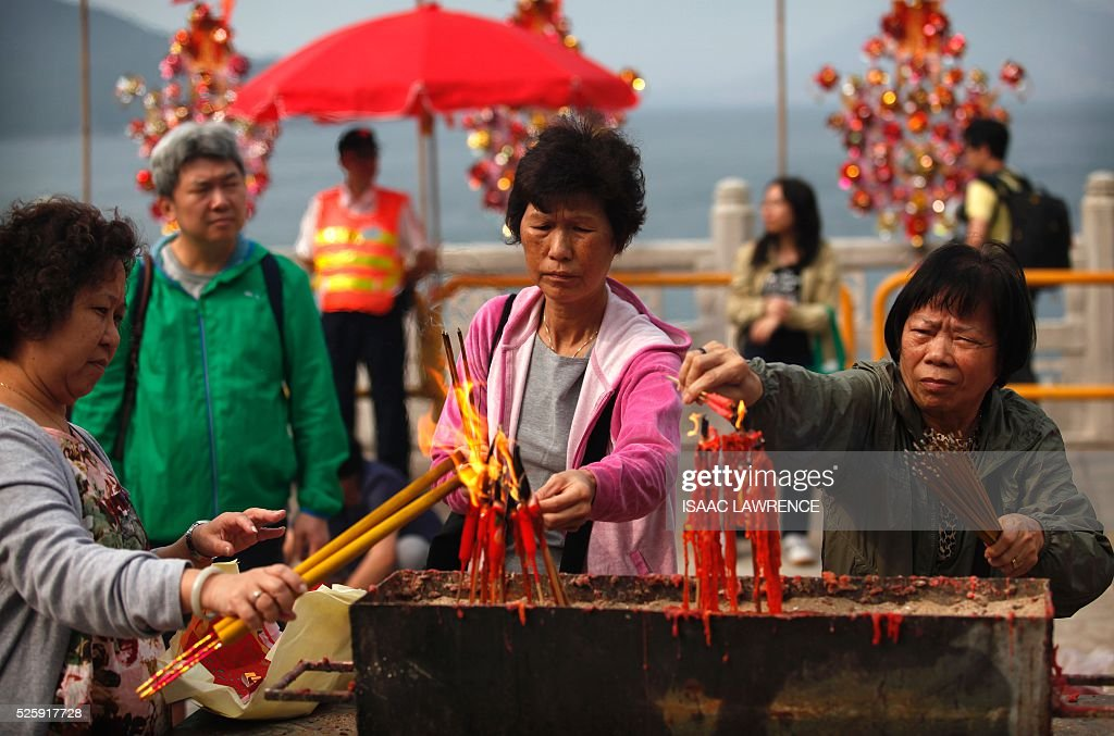 People light joss sticks outside the Joss House Bay Tin Hau temple during celebrations for the Tin Hau Festival in Hong Kong on April 29, 2016. Tin Hau is the Goddess of the Sea and patron saint of fishermen - On her birthday, locals flock to the more than 70 temples dedicated to her to pray for safety, security, fine weather and full fishing nets during the coming year. / AFP / ISAAC