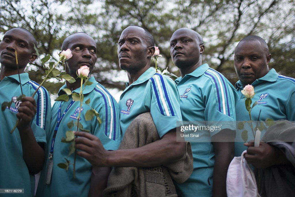 People light lay flowers for the victims of the Westgate Shopping Centre attack on September 28, 2013 in Nairobi, Kenya. Officials begun the task of forensic probing the Westgate shopping mall following a four-day siege that killed at least 67 civilians and police and was claimed by the Somali militant group al Shabaab.