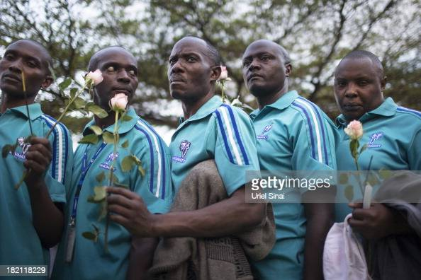 People light lay flowers for the victims of the Westgate Shopping Centre attack on September 28 2013 in Nairobi Kenya Officials begun the task of...