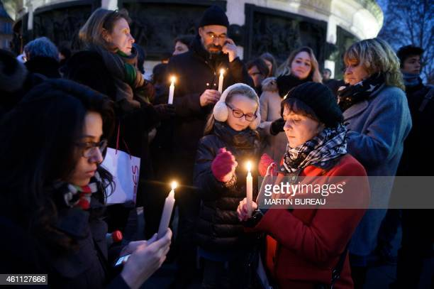 People like candles during a rally in support of the victims of the attack by gunmen at French satyrical newspaper Charlie Hebdo at the Place de la...