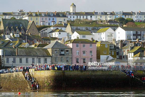 People line the harbour wall to watch the arival of yachtwoman Ellen MacArthur on board her giant trimaran as she returns to Falmouth harbour after...