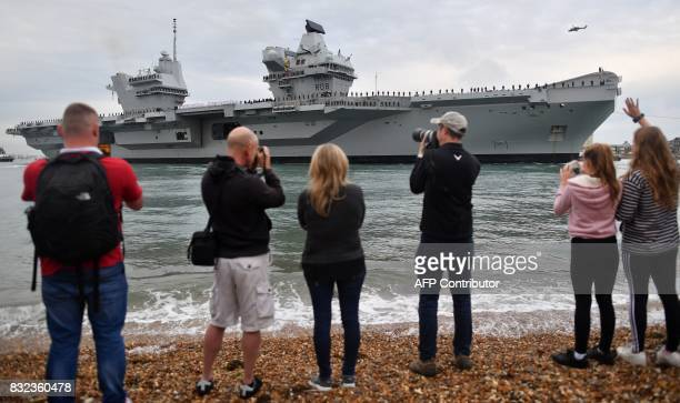 People line the shore to watch as tug boats manoeuvre the 65000tonne British aircraft carrier HMS Queen Elizabeth into Portsmouth Harbour in...