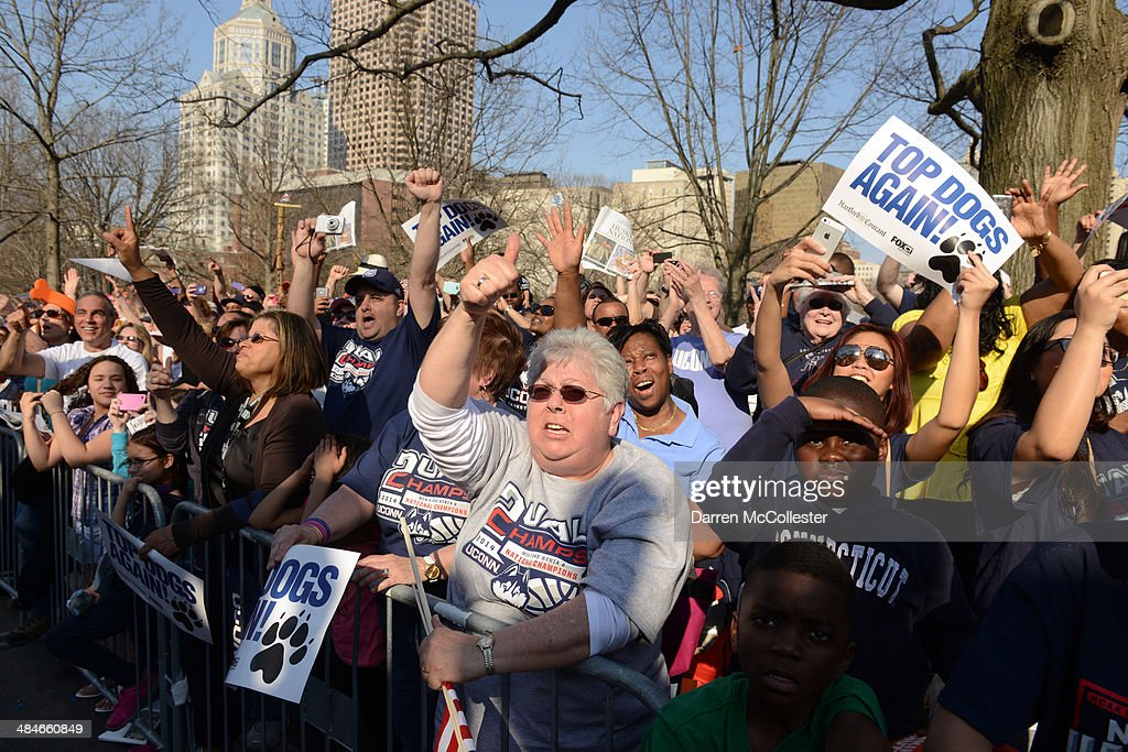 People line the sidewalk and cheer as the University of Connecticut's men's and women's basketball teams pass by during a victory parade to celebrate their national championships April 13, 2014 in Hartford, Connecticut. This year was the second time both the men's and women's Uconn basketball teams have won national championships in the same year.
