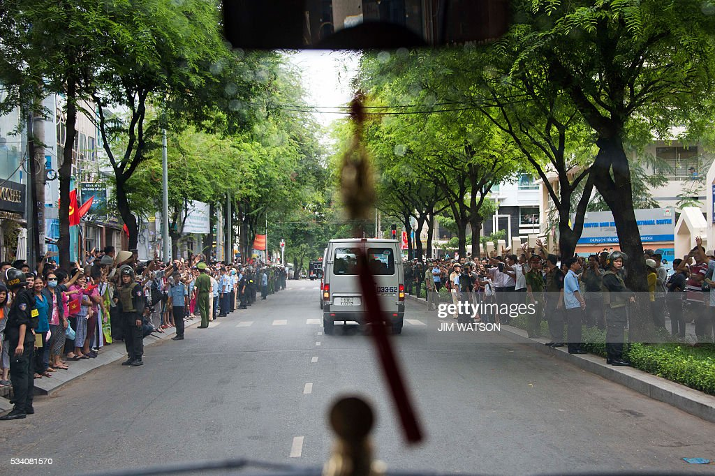 People line the street as US President Barack Obama's motorcade drives through Ho Chi Minh City on May 25, 2016. Obama urged communist Vietnam on May 24 to abandon authoritarianism, saying basic human rights would not jeopardise its stability, after Hanoi barred several dissidents from meeting the US leader. / AFP / JIM