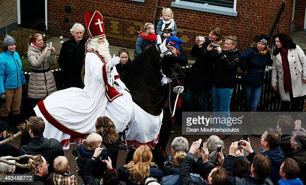 People line the streets near the pier as Sint Piter named after the patron saint of fishermen Saint Peter and Zwarte Piet arrive much to the delight...