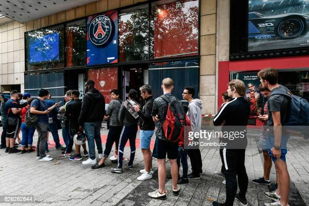 People line up as they wait for the opening of the ParisSaintGermain football club store on the Champs Elysees avenue in Paris on August 4 2017 Paris...