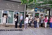 People line up at an ATM machine outside a bank on July 6 2015 in Athens Greece Politicians in Europe and Greece are planning emergency talks after...