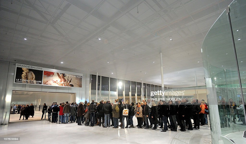 People line up at the Louvre Museum on the first day of its opening to the public, on December 4, 2012 in Lens, northern France. The Louvre museum opened a new satellite branch among the slag heaps of a former mining town Tuesday in a bid to bring high culture and visitors to one of France's poorest areas. Greeted by a group of former miners in overalls and hardhats, President Francois Hollande inaugurated today the Japanese-designed glass and polished-aluminium branch of the Louvre in the northern city of Lens. The 150 million euro ($196 million) project was 60 percent financed by regional authorities in the Nord-Pas-De-Calais region, on the English Channel and the border with Belgium. AFP PHOTO PHILIPPE HUGUEN