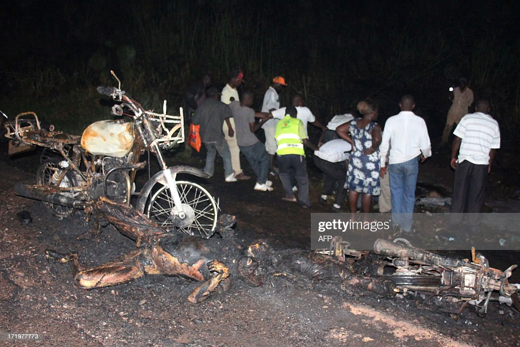 People line up bodies after a traffic accident involving a fuel tanker and a car on June 29, 2013 in Namungoona, a Kampala suburb. 31 people have so far been pronounced dead and many others are in the hospital with severe injuries, according to a police report. AFP PHOTO / ISAAC KASAMANI
