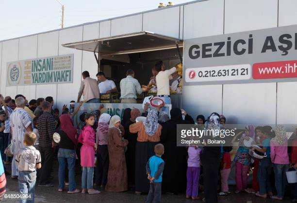 A'ZAZ ALEPPO SYRIA People line up for food distribution at the Syrian refugee camp near the border with Turkey in A'zaz Syria
