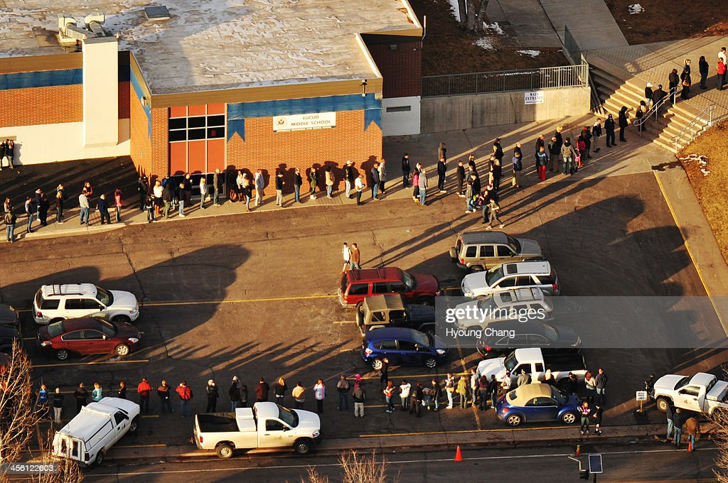 People line up outside of Euclid Middle School, one of the reunification centers, following a shooting incident at Arapahoe High School. A student carried a shotgun into Arapahoe High School and shot two fellow students in Centennial, Colorado December 13, 2013.