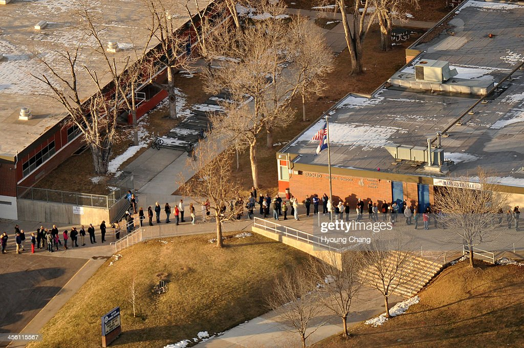 People line up outside of Euclid Middle School, one of the reunification centers, with their families following a shooting incident at Arapahoe High School. A student carried a shotgun into Arapahoe High School and shot two fellow students in Centennial, Colorado December 13, 2013.