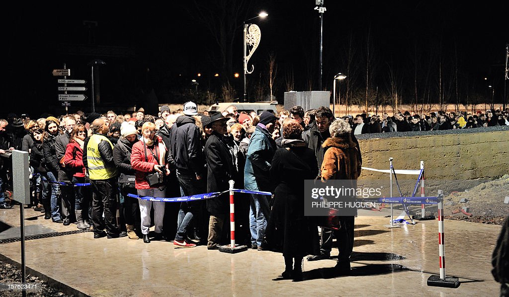 People line up outside the Louvre Museum on the first day of its opening to the public, on December 4, 2012 in Lens, northern France. The Louvre museum opened a new satellite branch among the slag heaps of a former mining town Tuesday in a bid to bring high culture and visitors to one of France's poorest areas. Greeted by a group of former miners in overalls and hardhats, President Francois Hollande inaugurated today the Japanese-designed glass and polished-aluminium branch of the Louvre in the northern city of Lens. The 150 million euro ($196 million) project was 60 percent financed by regional authorities in the Nord-Pas-De-Calais region, on the English Channel and the border with Belgium. AFP PHOTO PHILIPPE HUGUEN