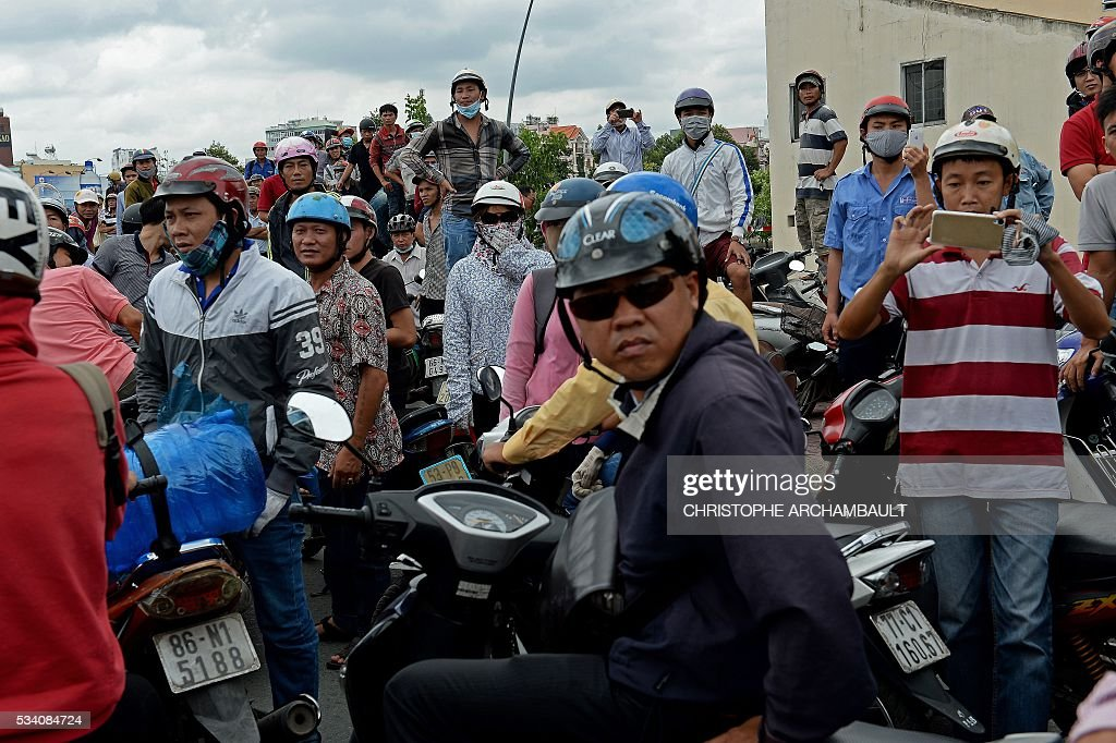 People line up the streets to catch a glimpse of US President Barack Obama on his way to the airport at the end of two-day visit to Ho Chi Minh City on May 25, 2016. Obama fielded questions on May 25 on everything from rap and weed smoking to leadership and his good looks at a lively town hall-style meeting with young Vietnamese, who say the US leader is a far cry from their staid Communist rulers. / AFP / CHRISTOPHE