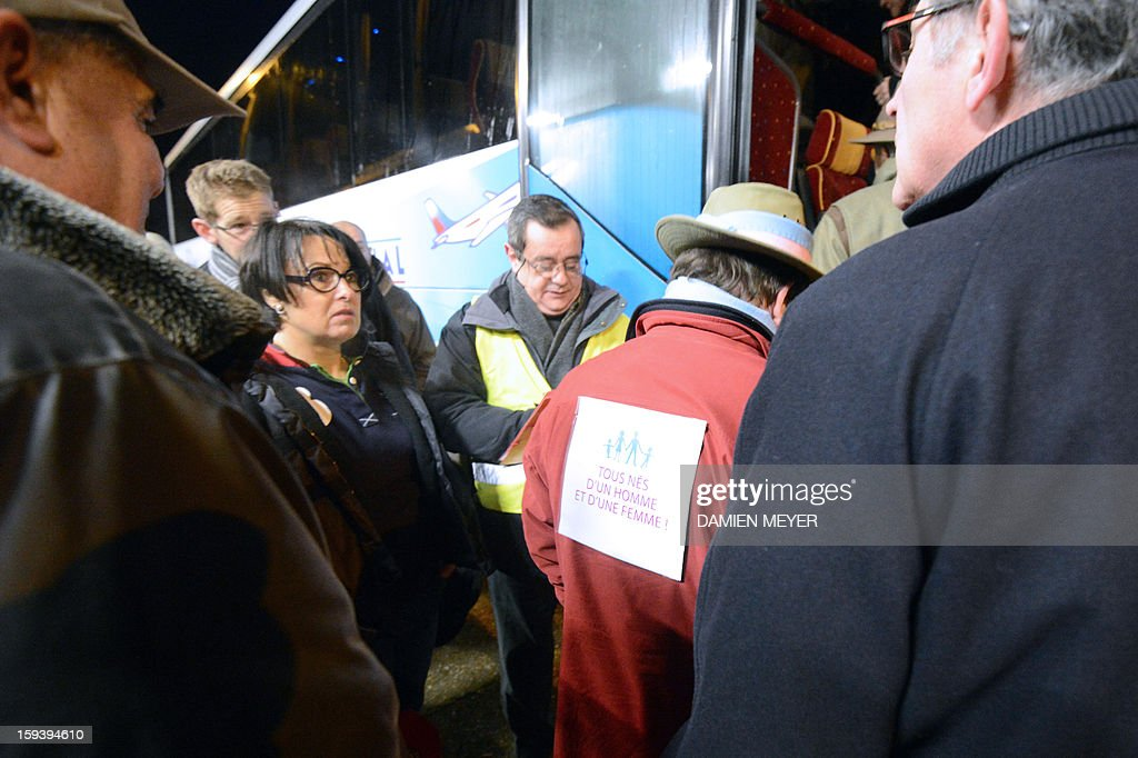 People line up to board a bus to Paris, in the early morning on January 13, 2013, outside the railway station in Avranches, in western France, to attend Paris' demonstration against same-sex wedding. Tens of thousands are set to march in Paris on January 13 to denounce government plans to legalise same-sex marriage and adoption, which have angered many Catholics and of the right-wing opposition. Placard at center reads : ''All born of a man and a woman.'