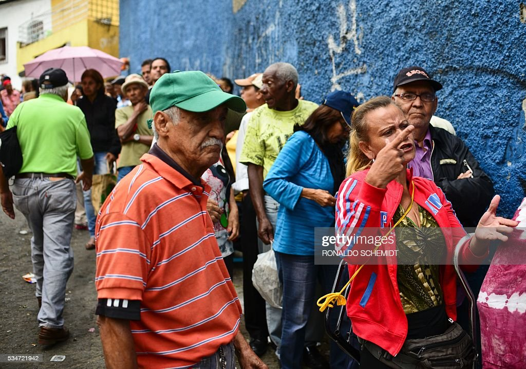 People line up to buy basic food and household items outside a supermarket in the poor neighborhood of Lidice, in Caracas, Venezuela on May 27, 2016. / AFP / RONALDO