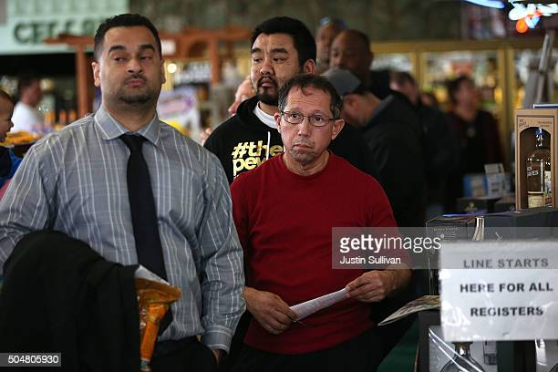 People line up to buy Powerball tickets at Kavanagh Liquors on January 13 2016 in San Lorenzo California Dozens of people lined up outside of...