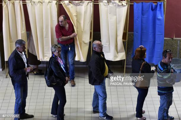 People line up to cast they votes at a polling station in MartresTolosane southwestern France on April 23 during the first round of the French...