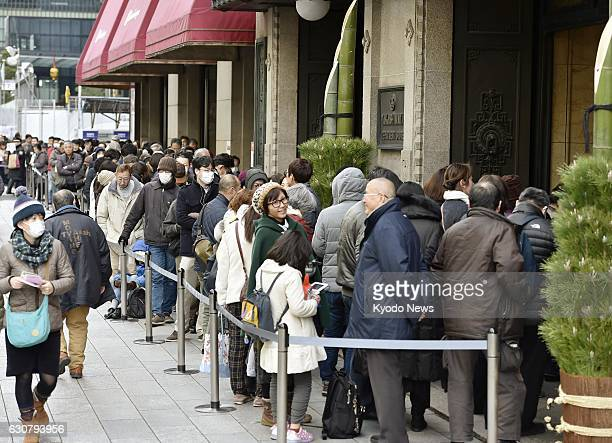 People line up to enter the Nihombashi store of Takashimaya department store chain in Tokyo on Jan 2 2017 Japanese department stores opened for the...