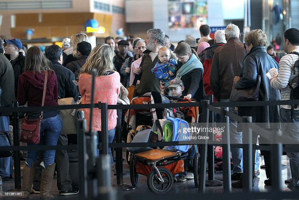 People line up to go through security in Terminal A as Logan Airport is reopened for the first full day, on Sunday, February 10, 2013, after the blizzard.