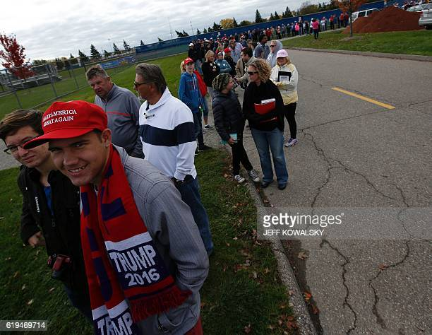 People line up to see US Republican Presidential nominee Donald Trump speak at Macomb Community College on October 31 2016 in Warren Michigan / AFP /...