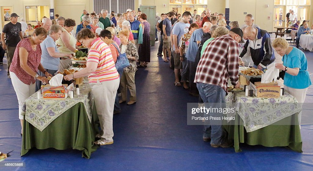 People line up to serve themselves buffetstyle at a free community dinner at Freyburg Academy in Fryeburg on Tuesday August 25 2015 Weston's Farm a...