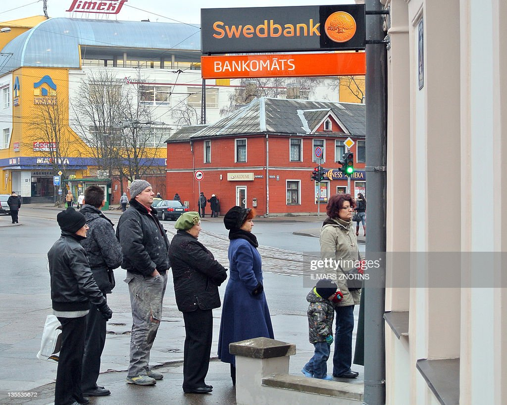 People line up to withdraw cash at a Swedbank automatic teller machine (ATM) in Riga on December 12, 2011. More than 100 cashpoints in Latvia had run out of money on December 12 following a banking panic apparently caused by rumors on the Twitter social media network. A total of 126 out of 298 ATMs belonging to Swedbank, the country's biggest lender, had run dry after demand for cash soared 10-fold late on December 11, according to a statement on the Swedish-owned bank's homepage. AFP PHOTO / ILMARS ZNOTINS