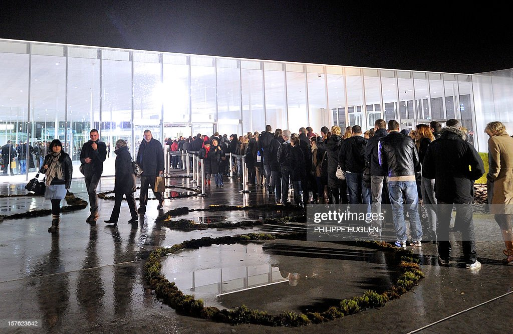 People lineup outside the Louvre Museum on the first day of its opening to the public, on December 4, 2012 in Lens, northern France. The Louvre museum opened a new satellite branch among the slag heaps of a former mining town Tuesday in a bid to bring high culture and visitors to one of France's poorest areas. Greeted by a group of former miners in overalls and hardhats, President Francois Hollande inaugurated today the Japanese-designed glass and polished-aluminium branch of the Louvre in the northern city of Lens. The 150 million euro ($196 million) project was 60 percent financed by regional authorities in the Nord-Pas-De-Calais region, on the English Channel and the border with Belgium.