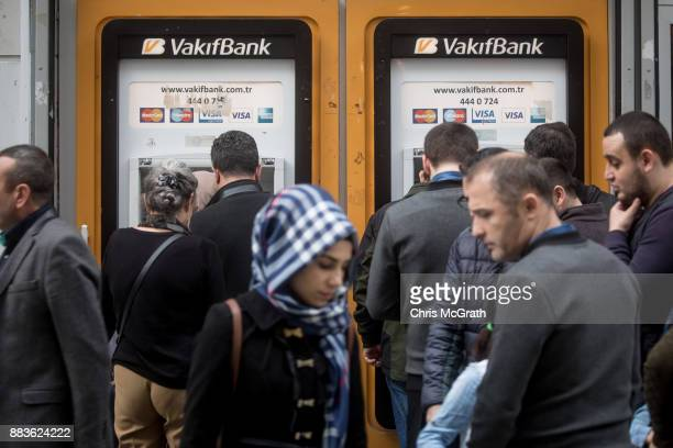 People lineup to use ATM machines at a branch of Turkish bank VakifBank on December 1 2017 in Istanbul Turkey The trial of Mr Reza Zarrab an...