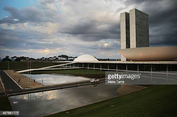 People linger in front of the Brazilian National Congress building on October 27 2014 in Brasilia Brazil Brazil's leftwing President Dilma Rousseff...
