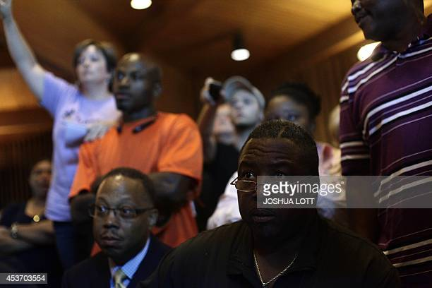 People listen as Missouri Governor Jay Nixon speaks about the shooting death of 18 yearold Michael Brown during a news conference August 16 2014 in...
