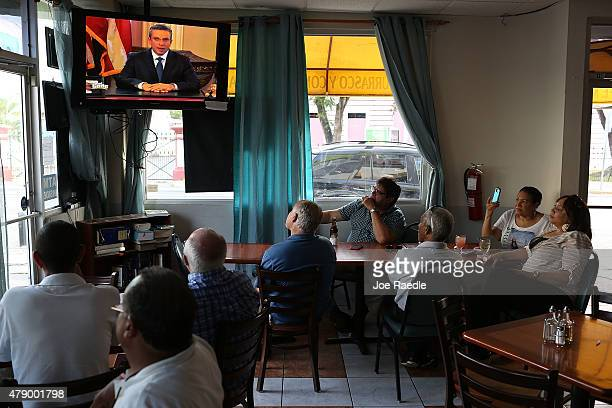 People listen as Puerto Rican Governor Alejandro Garcia Padilla addresses the island's residents in a televised broadcast regarding the governments...