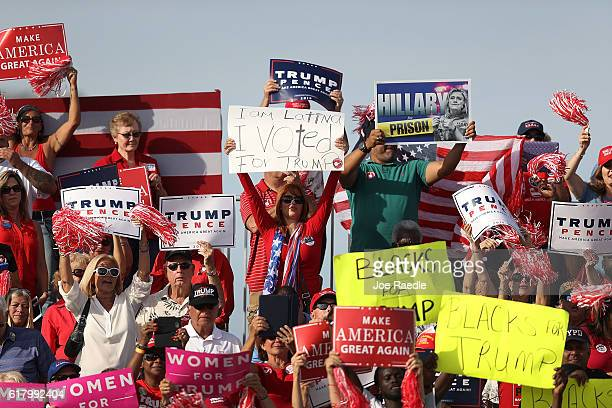 People listen as Republican presidential candidate Donald Trump speaks during a campaign rally at the Million Air Orlando which is at Orlando Sanford...