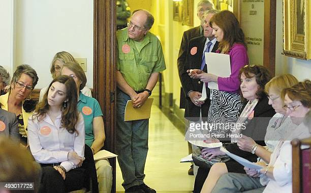 People listen in from the hallway outside the Judiciary Committee room during a hearing on Tuesday afternoon at the State House in Augusta on three...