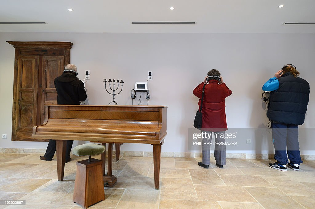 People listen music as they visit the 'Maison Jean Ferrat' in the southern French city of Antraigues-sur-Volane, on March 13, 2013, during its opening three years after French singer-songwriter Jean Ferrat died. As prolific as he was discreet, Ferrat wrote and performed about 200 songs which reflected his political views, his affection for the poet and novelist Louis Aragon, and his love for his adopted Ardeche region.